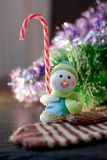 Toy snowman holding christmas candy cane in hands. Toy snowman holding christmas candy cane in hands Stock Photos