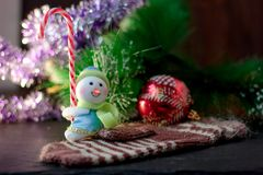 Toy snowman holding christmas candy cane in hands. Toy snowman holding christmas candy cane in hands Royalty Free Stock Photography