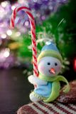 Toy snowman holding christmas candy cane in hands. Toy snowman holding christmas candy cane in hands Stock Image