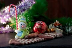 Toy snowman holding christmas candy cane in hands. Toy snowman holding christmas candy cane in hands Royalty Free Stock Photo
