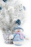 Toy snowman next to a white Christmas tree. Cute Toy snowman next to a white Christmas tree Stock Photo