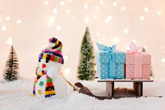 Toy snowman pulling small wooden sleigh with a Christmas gifts. Stock Photography