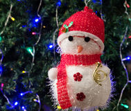 Toy snowman in red hat. On a background of Christmas trees decorated with garland Royalty Free Stock Images