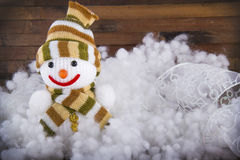 Toy snowman in the snow on the wooden background Stock Images