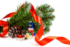 Toy snowman under a branch of an artificial Christmas tree with the cone Royalty Free Stock Images