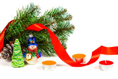 Toy snowman under a branch of an artificial Christmas tree with the cone Stock Images