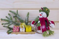 Toy Snowman unter Tannenbäumen und Geschenken Stockfoto