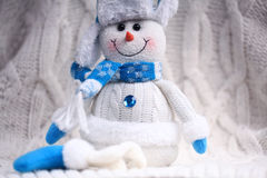 Toy snowman at white knitted background Royalty Free Stock Image