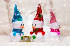 Toy snowmen on the background of snow during the snowfall. Two snowmen talking, the third offended turned away_ royalty free stock photos