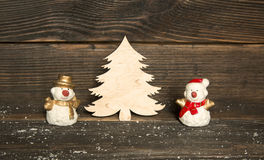 Toy snowmen and wooden Christmas tree on a dark wooden backgroun Stock Images