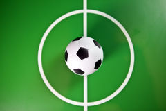 Toy soccerball in a midfield, in the center of the green field Stock Images