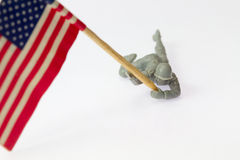 Toy soldier. A close up of toy soldier holding up the american flag stock photo