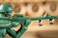Close up toy soldier with tank reflection in drops. Toy soldier with assault rifle Royalty Free Stock Photo