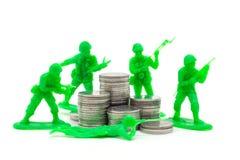 Toy Soldier auf Münze stapelt einen weißen Hintergrund Lizenzfreies Stockfoto