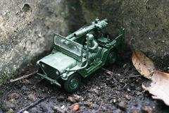 Toy soldier drive his jeep on a soak soil ground Royalty Free Stock Photography