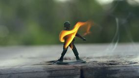 Toy soldier on fire. Slow motion stock video