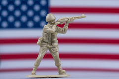 Toy soldier in front of American flag with desert brown color. A toy soldier in desert color uniform stands with gun and the American Flag blurred in background Stock Image