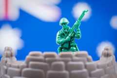 Toy soldier in front of Australian flag. Toy soldier stands with gun in front of a blurred Australian flag Royalty Free Stock Image