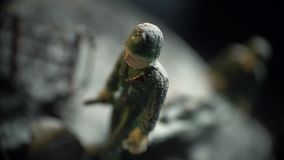 Toy soldier in green uniform. A toy soldier in uniform walks through a snow-covered field stock video