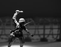 Toy Soldier with Grenade. Close-Up of a Toy Soldier with Grenade with barbed wire in the background Royalty Free Stock Images