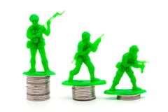 Toy Soldier på mynt staplar en vit bakgrund royaltyfri foto