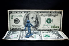 Toy soldier standing with dollar Stock Image