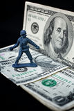 Toy soldier standing with dollar Stock Photos