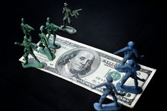 Toy soldier standing with dollar Stock Images