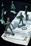 Toy soldier standing with dollar Royalty Free Stock Images