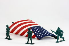 Toy Soldiers Protecting American Flag. Three little green toy soldiers surround a small American flag on a white background Royalty Free Stock Photography