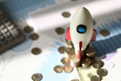 Toy space rocket stands on coins near calculator