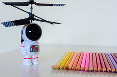Toy Spaceman des Kindes, der in Richtung eines Satzes bunten Bleistiftcr blickt Stockfotografie