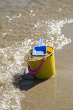 Toy Spade and Bucket on a Beach Shore Royalty Free Stock Images