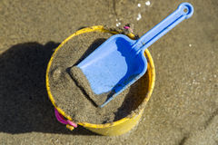Toy Spade and Bucket on a Beach Shore Stock Image