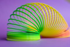 Toy spring on purple background. Royalty Free Stock Photos