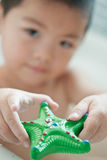 A toy starfish. An asia boy with a toy starfish Royalty Free Stock Image