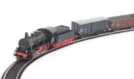 Toy steam locomotive and freight cars on white. Background Royalty Free Stock Images