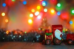 Toy Steam Train met Santa Claus bij een achtergrond van gouden slingers en het onduidelijke beeld van gekleurde lichten stock afbeeldingen