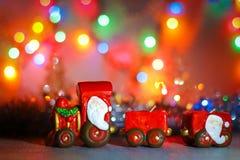Toy Steam Train met Santa Claus bij een achtergrond van gouden slingers en het onduidelijke beeld van gekleurde lichten royalty-vrije stock afbeeldingen