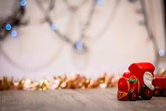 Toy Steam Train met Santa Claus bij een achtergrond van gouden slingers en het onduidelijke beeld van gekleurde lichten royalty-vrije stock fotografie