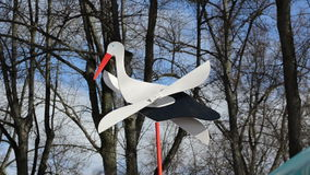 Toy stork on shaft with wooden wings easily rotating in wind stock video footage