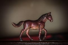 Toy strong horse runs along the road royalty free stock photography