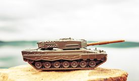 Toy tank on nature background with blue sky and lake royalty free stock images