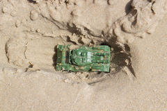 Toy Tank. Buried in the sand on the beach Stock Photo