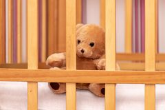 Toy teddy bear in a baby cot stock images