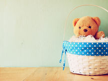 Toy teddy bear in basket on wooden table. retro filtered image royalty free stock images