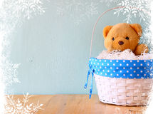 Toy teddy bear in basket on wooden table with snowflake overlay Stock Image