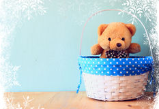 Toy teddy bear in basket on wooden table with snowflake overlay. Stock Photography