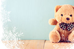 Toy teddy bear in basket on wooden table with snowflake overlay Royalty Free Stock Photos