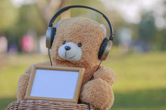 Toy teddy bear hearing music with wooden photo frame with wooden Stock Images